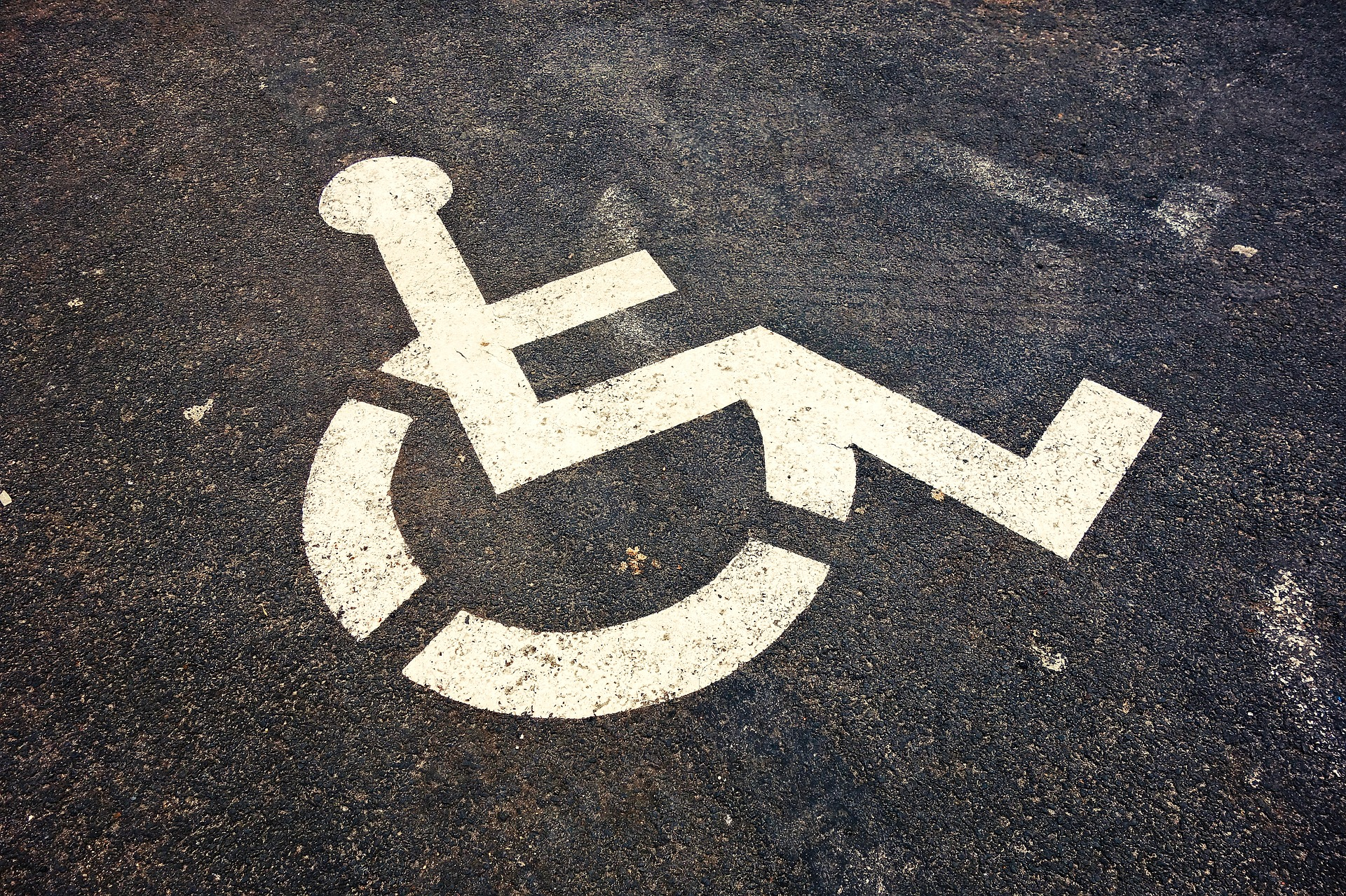 image of wheelchair accessibility icon on pavement.