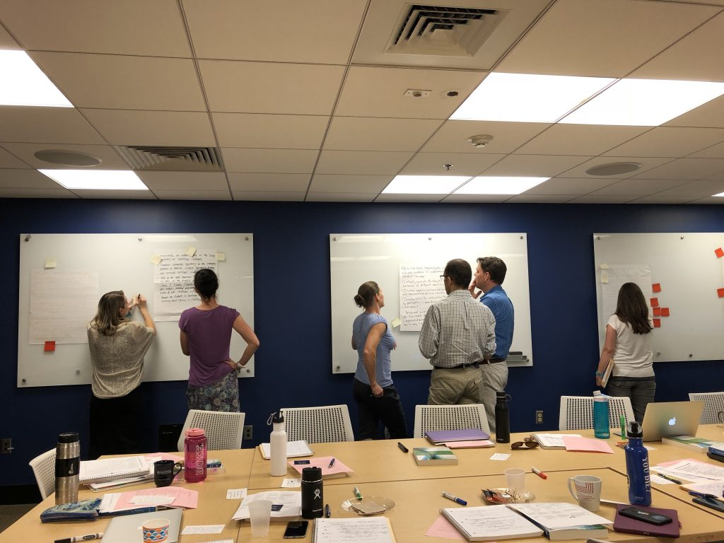 faculty participants doing a group activity at whiteboards