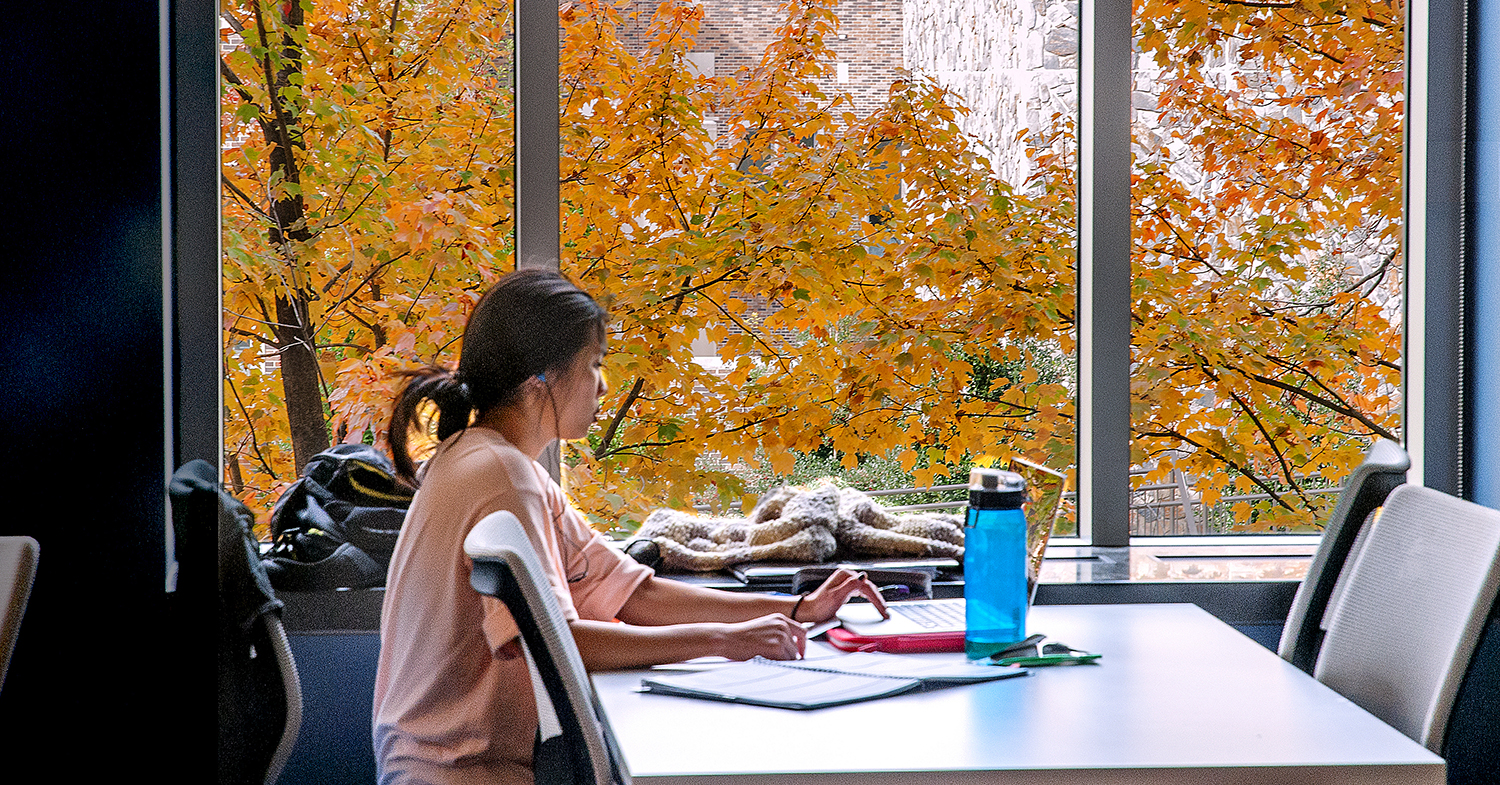 Girl studying by window with fall foliage.