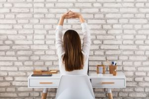 Rear View Of A Woman Stretching Her Arms at Desk