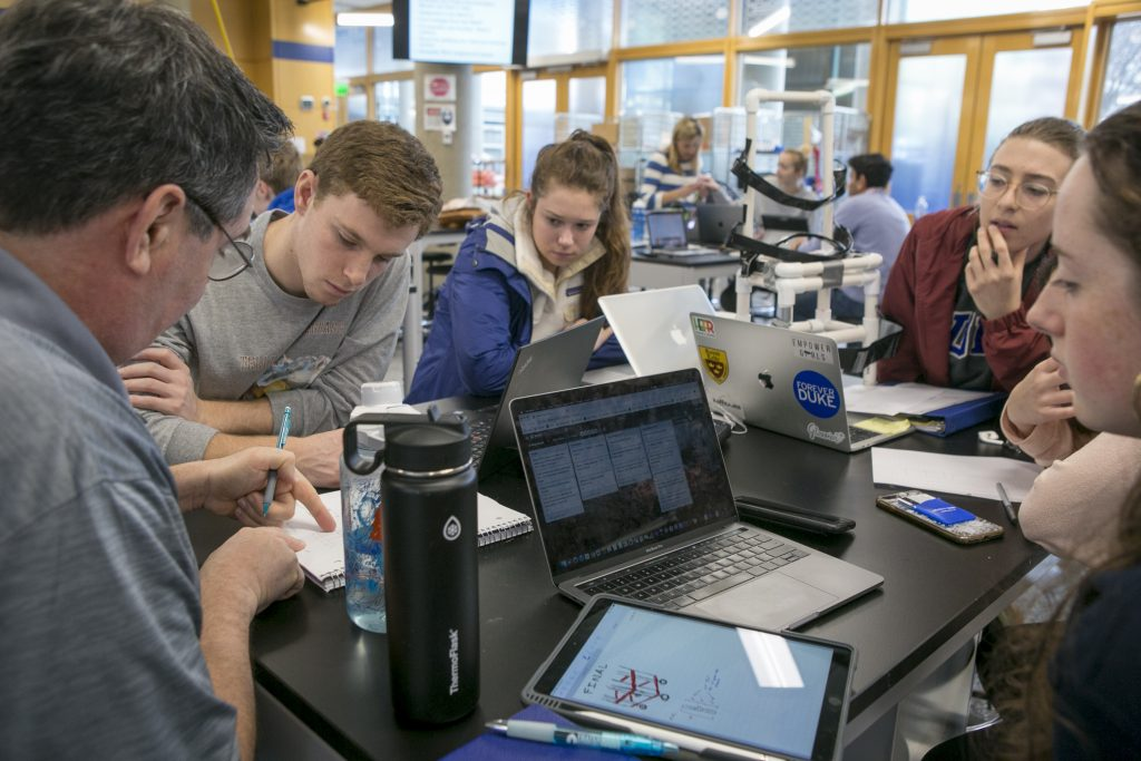 A professor explains something to a group of students using computers and an iPad.