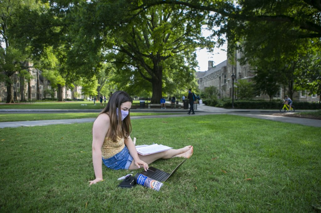 Masked girl sits on grass working on her laptop outside.